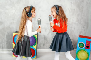Funny kids singing and listening to music on headphones. The concept is childhood, lifestyle, dance, music.