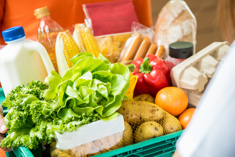 Delivery man delivering food to customer at home - online grocery shopping service concept
