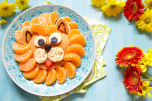 Funny lion pancake with mandarins and berries