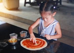 Little asian child girl making pizza.