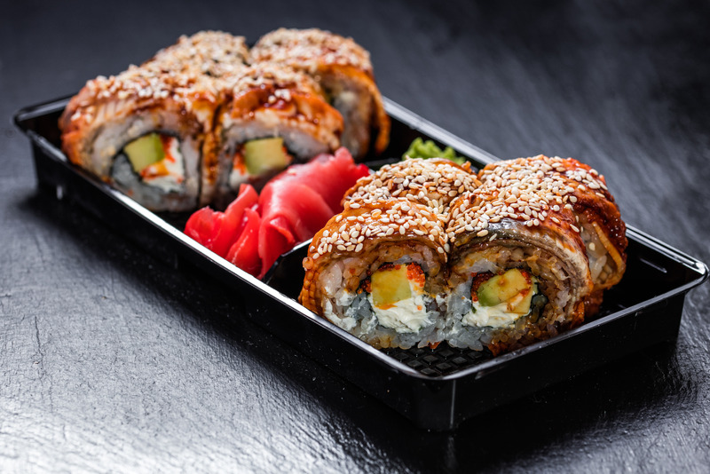 Unagi philadelphia makizushi american-style roll in a take-away delivery container