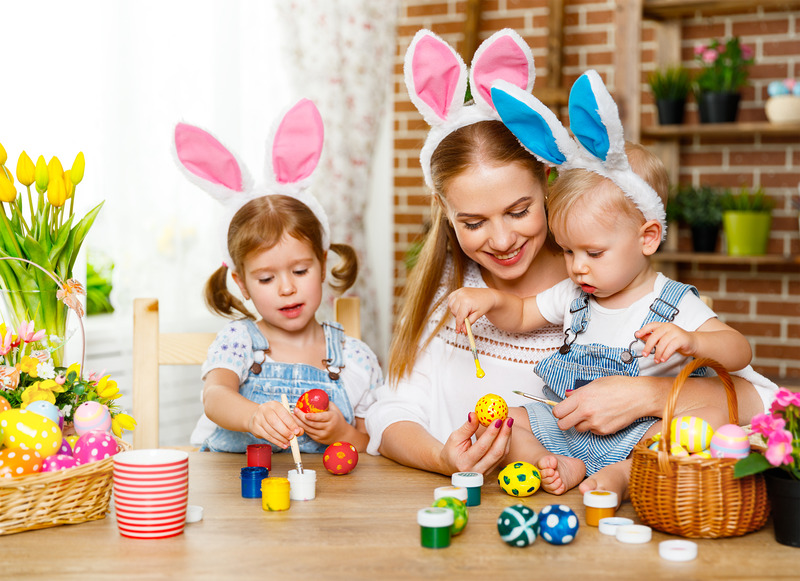 Happy easter! family mother and children paint eggs for holiday Easter at home