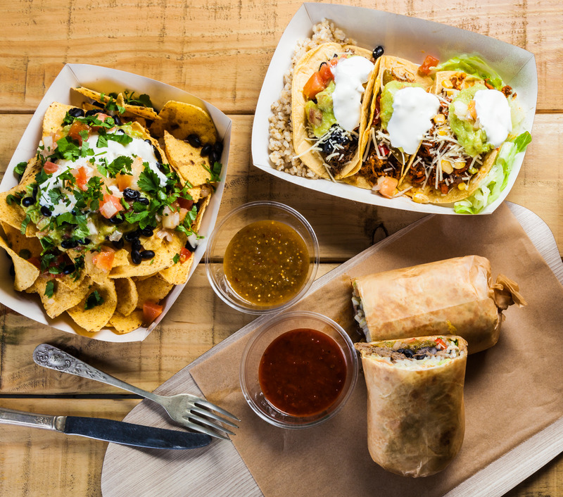 Takeaway Mexican food: burrito, nachos, tacos and spicy sauce.