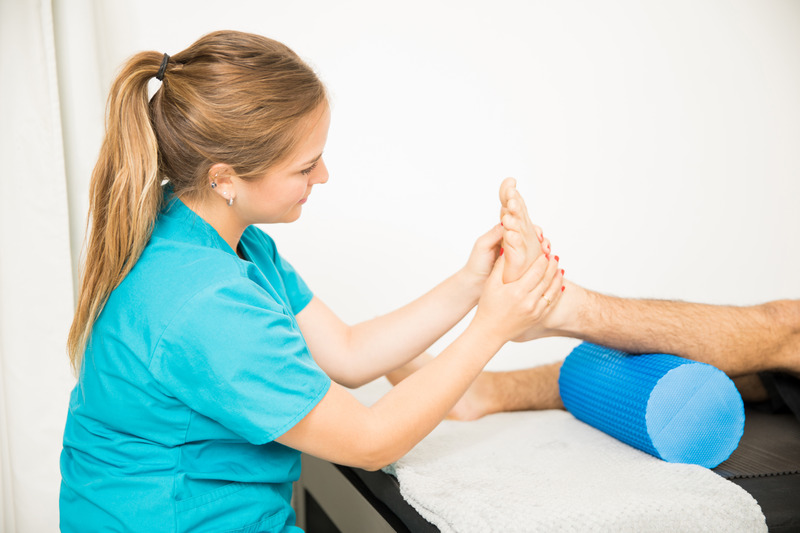 Female physiotherapy professional massaging patient's foot in clinic