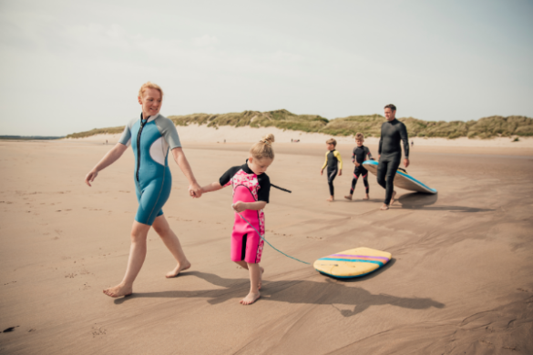family together on a surfing holiday in wetsuits