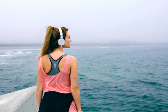 woman with headphones staring at the ocean