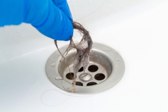 gloved hand pulling hair from drain